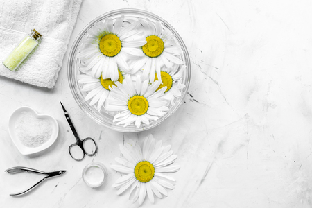 Spa composition on white desk with chamomile, towel and manicure set copyspase top view. Stock Photo