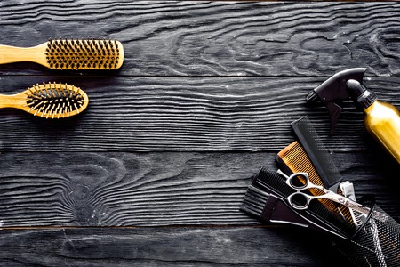 Brushes, hairdryer and hairspray on grey wooden background top view space for text Фото со стока