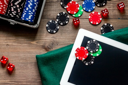 Compulsive gambling. Poker chips and the dice nearby tablet on wooden table top view Stock Photo