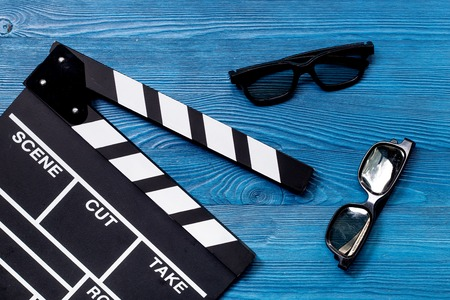 Attributes of film director. Movie clapperboard and sunglasses on blue wooden table background top view