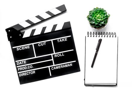 Werktafel van producent. Film clapperboard en notitieboekje op witte hoogste mening als achtergrond Stockfoto