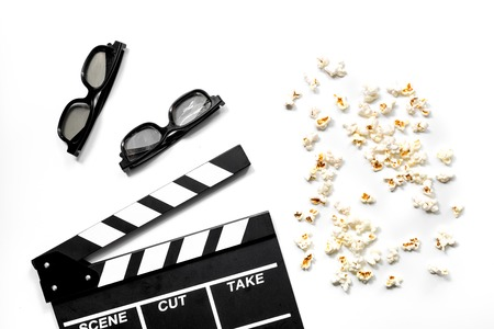 Watching the film. Movie clapperboard, sunglasses and popcorn on white background top view Stock Photo