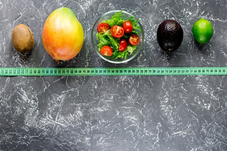 Healthy diet. Salad with fresh products and fruits mango, mangosteen, kiwi and measuring tape on stone table top view Stock Photo