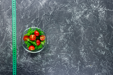 Slimming diet. Salad and measuring tape on grey table background top view copyspace Stock Photo