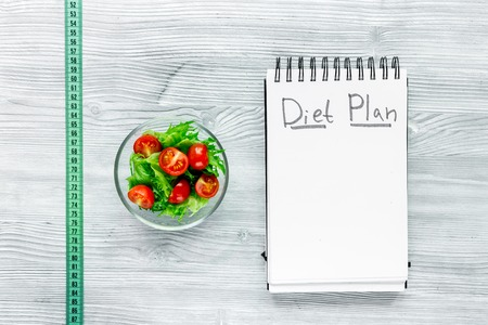 Notebook for diet plan, salad and measuring tape on grey wooden table top view mock up.