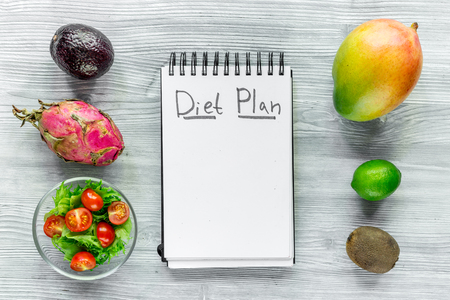Heathy food for slimming. Notebook for diet plan, fruits and salad on grey wooden table top view mock up Stock Photo - 80892145