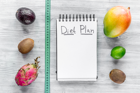 Tasty food for slimming. Notebook for diet plan and fruits on grey wooden table top view mock up Stock Photo