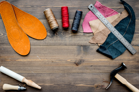 Working place of shoemaker. Skin and tools on brown wooden desk background top view. Stock Photo