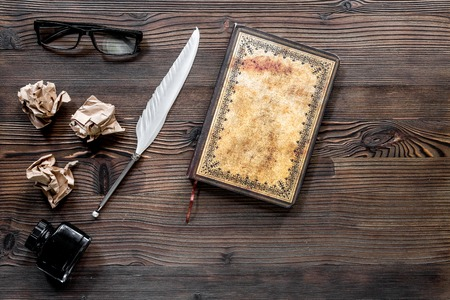 Writer concept. Feather pen, vintage notebook and crumpled paper on wooden table background top view copyspace