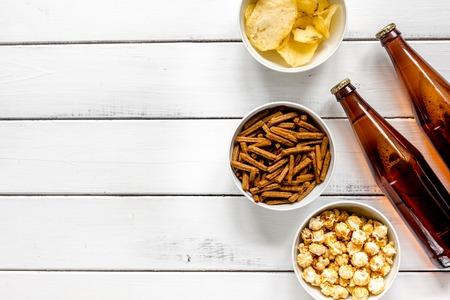 Regarder la télévision avec des chips, de la bière et du maïs soufflé sur la vue de dessus du fond blanc Banque d'images - 80892607
