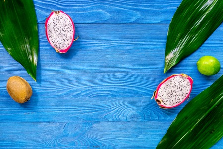 Exotic fruit meal. Dragonfruit, kiwi, lime on blue wooden table background top view copyspace Stock Photo