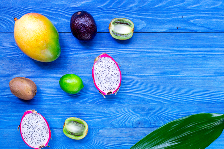 Exotic fruits. Dragonfruit, mangosteen, mango, kiwi and lime on blue wooden background top view copyspace