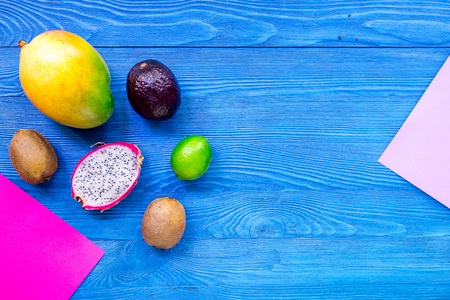 Exotic fruits dragonfruit, mangosteen, mango, kiwi and lime on blue wooden background top view copyspace Stock Photo