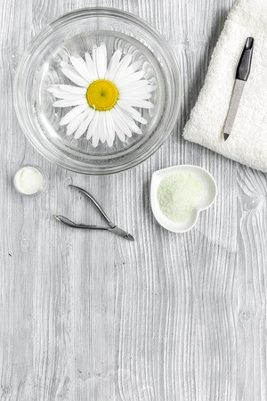Spa composition on wooden desk with chamomile, salt, towel and manicure set copyspase top view. Zdjęcie Seryjne