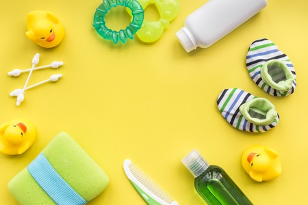 Bath cosmetic set for kids, towel and toys on yellow background top view space for text