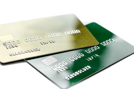 Werkplaats met bedrijfscreditcards voor betaling op witte bureau dichte omhooggaand als achtergrond