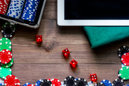 Poker chips and the dice nearby tablet on wooden table top view.