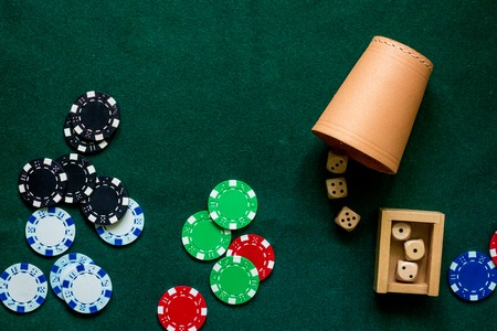 Poker chips and dices on a green gaming table top view copyspace close up