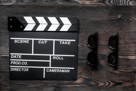 영화 감독의 속성. 영화 clapperboard 및 나무 테이블 배경 상위 뷰 선글라스