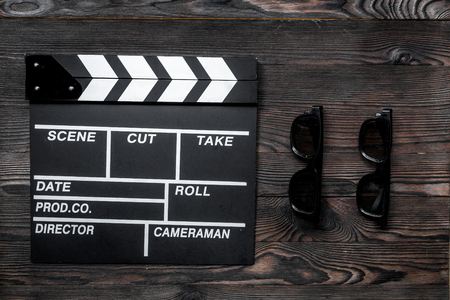 Attributes of film director. Movie clapperboard and sunglasses on wooden table background top view Reklamní fotografie - 80929784