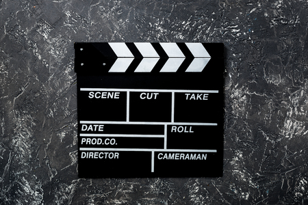 Movie clapperboard on grey stone table background top view copyspace