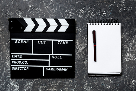 Work table of producer. Movie clapperboard and notebook on grey stone background top view Stock Photo