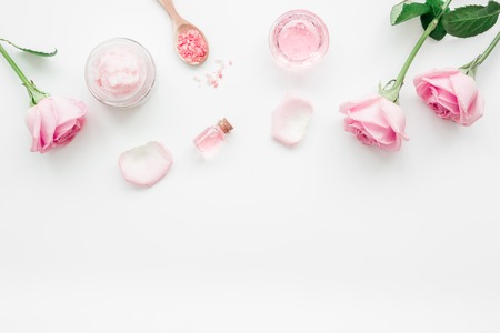 body treatment with rose flowers and cosmetic set white desk background top view space for text Stock Photo