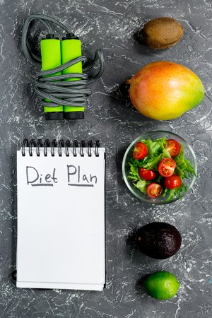 Slimming. Notebook for diet plan, fruits, salad and skipping rope on grey stone table top view mock up Stock Photo - 80929777