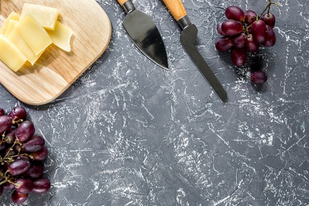 Aperitive parmesan cheese and red grape on grey stone table background copyspace top view