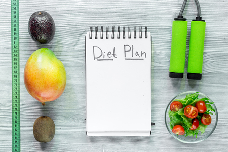 Heathy food for slimming. Notebook for diet plan, fruits and measuring tape on grey wooden table top view mock up