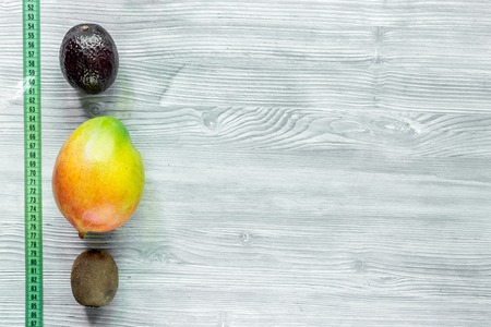 Slimming diet. Fruits mango, mangosteen, kiwi and measuring tape on grey wooden table top view copyspace Stock Photo - 80930979