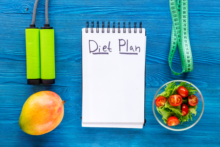 Tasty food for slimming. Notebook for diet plan, salad, fruits and measuring tape on blue table top view mock up