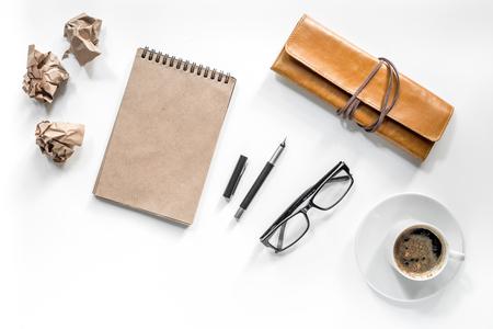 Schriftsteller-Zubehör Weinlesenotizbuch, Stift, zerknittertes Papier und coffeee auf weißem Draufsichtmodell des Hintergrundes