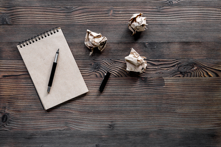 Writer concept. Vintage notebook and crumpled paper on wooden table background top view copyspace
