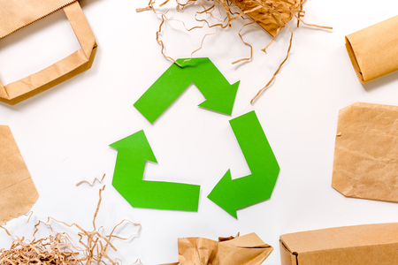 Paper recycle sign with paper and carton garbage on white background top view