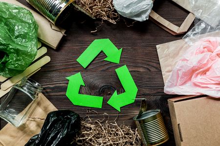 Garbage for recycling with recycling symbol on wooden background top view