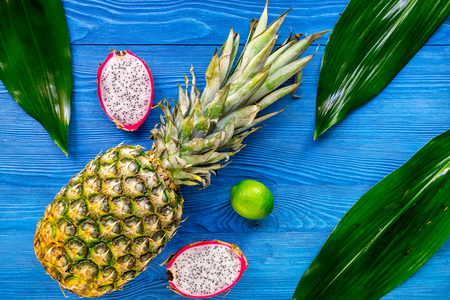 Pineapple, dragonfruit and lime on blue wooden desk background top view