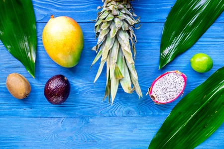 Exotic fruit meal. Dragonfruit, mangosteen, mango, kiwi, lime and pineapple on blue wooden background top view copyspace Stock Photo