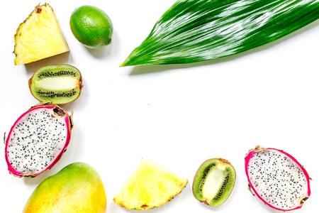 Set of exotic fruits. Dragonfruit, pineapple, mango, lime and kiwi on white background top view copyspace