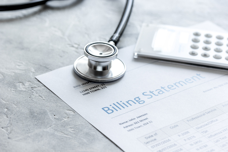 stethoscope, billing statement for doctors work in medical center stone background Stock Photo