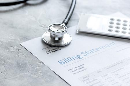 stethoscope, billing statement for doctors work in medical center stone background Standard-Bild
