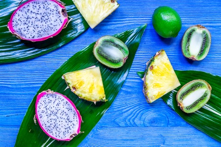 Pieces of exotic fruits. Dragonfruit, pineapple and kiwi on blue wooden background top view copyspace