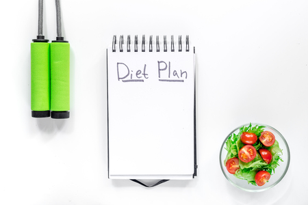 Notebook for diet plan, salad with fresh products and jump rope on white background top view mock up.