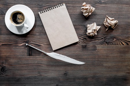 Writer concept. Feather pen, vintage notebook and crumpled paper on wooden table background top view copyspace mockup