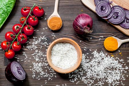 米、トマト、木製キッチン テーブル背景トップ ビューで玉ねぎと自家製パエリア成分組成