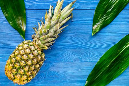 Ananas en bladeren op blauwe houten bureau hoogste mening als achtergrond copyspace
