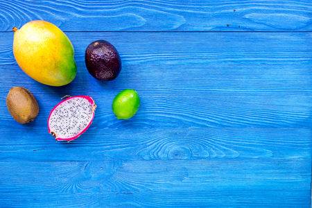 Exotic fruits dragonfruit, mangosteen, mango, kiwi and lime on blue wooden table background top view copyspace