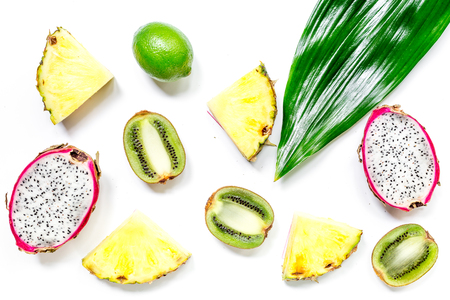 Pieces of exotic fruits. Dragonfruit, pineapple and kiwi on white background top view