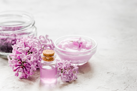 Organic salt, cream, extract in lilac cosmetic set with flowers on stone table background