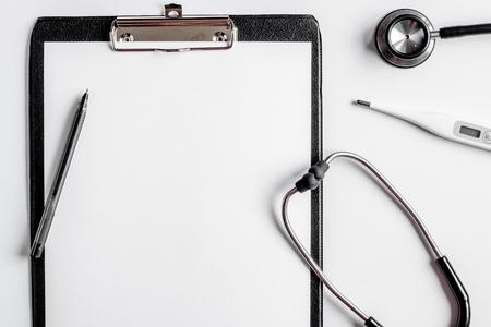 De moderne geneeskundewerkplaats met raad, vlakke de stethoscoop witte lijst legt ruimte voor tekst Stockfoto